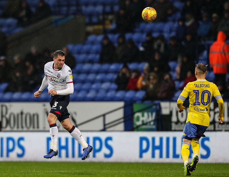 Bolton Wanderers' Andrew Taylor heads forward as  Leeds United's Ezgjan Alioski looks on<br /> <br /> Photographer Andrew Kearns/CameraSport<br /> <br /> The EFL Sky Bet Championship - Bolton Wanderers v Leeds United - Saturday 15th December 2018 - University of Bolton Stadium - Bolton<br /> <br /> World Copyright © 2018 CameraSport. All rights reserved. 43 Linden Ave. Countesthorpe. Leicester. England. LE8 5PG - Tel: +44 (0) 116 277 4147 - admin@camerasport.com - www.camerasport.com