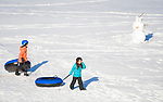 COLEBROOK, CT-012118JS02--Kids walk their tubes past a snowman after finishing a run while tubing Sunday at Camp Jewell in Colebrook. The YMCA camp offers free community tubing on Sunday's from 2-4 p.m. weather permitting. <br /> Jim Shannon Republican-American