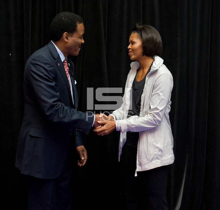 First Lady Michelle Obama stands with President and CEO of the US Soccer Foundation Ed Foster-Simeon during a US Soccer Foundation clinic held at City Center in Washington, DC.