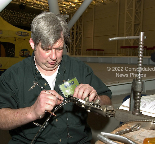 "Museum Specialist Scott Wood demonstrates a ""Five-Tuck Navy Splice"" as part of the first anniversary festivities of the Smithsonian National Air and Space Museum Steven F. Udvar-Hazy Center in Chantilly, Virginia on December 11,2004.  This splice is one of only two splices approved by the Civil Air Regulations for use on control cables over 1/16 inch in diameter.  The work is complex and technicians are cautioned that ""a number of practice splices should be made before doing any of this work on an airplane which is to be flown""..Credit: Ron Sachs / CNP.(RESTRICTION: NO New York or New Jersey Newspapers or newspapers within a 75 mile radius of New York City)"