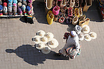 A man selling rugs walks through the market in Marrakesh, Morocco and passes other vendors selling straw bags, straw hats, and more..