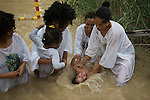 A woman baptises her daughter, as orthodox-Christian pilgrims of Eritrean and Ethiopian descent, living as migrants in Tel Aviv, Israel, baptise during Epiphany holiday, at the baptismal site of Qasr el-Yahud on the Jordan River, near the West Bank town of Jericho. The site is believed to be where Jesus was baptised by John the Baptist.