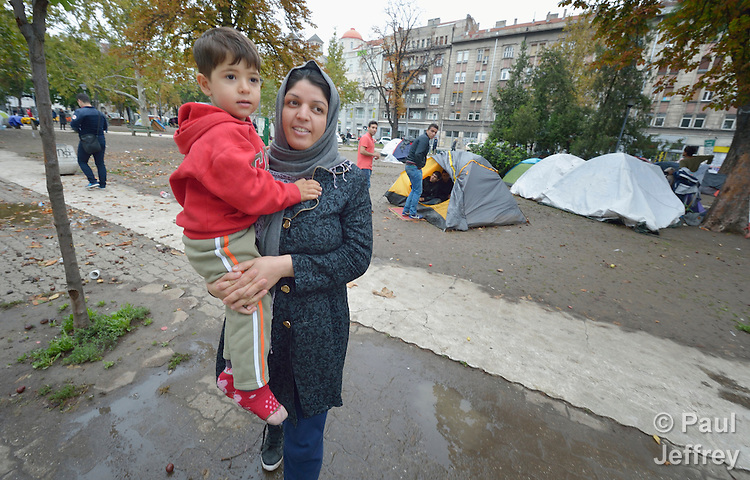 Somaye carries her four-year old son Elyas in a city park in Belgrade, Serbia. They fled violence in Herat, Afghanistan, and set off for western Europe. The park has filled with refugees from Syria, Afghanistan and other countries stopping over on their way to Germany, Holland, Sweden, and other countries.