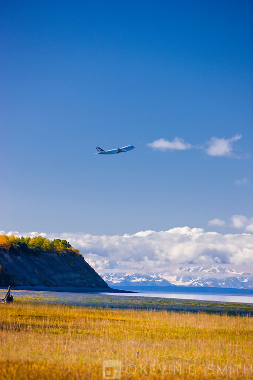 Plane taking off from Ted Stevens International Airport flying above Point Wornzof, Alaska Range in the background, Anchorage, Southcentral Alaska, USA.