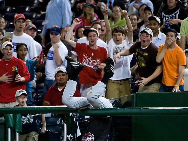 Democrats first baseman Bart Stupak, D-Mich., flips over the rail while chasing down a pop foul ball in the Congressional Baseball Game at Nationals Stadium in Washington on June 17, 2009.