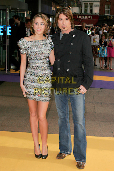 "MILEY CYRUS & BILLY RAY CYRUS.UK Premiere of ""Hannah Montana: The Movie"" at the Odeon Leicester Square, London, England. .April 23rd 2009 .full length silver grey gray beaded beads embellished jewel encrusted dress shoulder pads structured shoulders sculpted bracelets bangles jeans denim black jacket father dad daughter family  shoes .CAP/AH.©Adam Houghton/Capital Pictures."