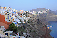 Whitewashed houses on top of the cliff. Port with the ferry in Oia village, Santorini