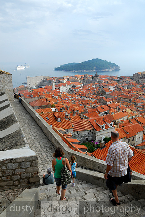 People walking down very steep steps of Minceta Tower, looking over tiled roofs of Dobrovnik old town, Croatia