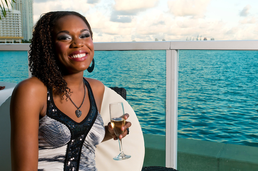 Young african american enjoys a galss of champagne in an outdoor terrace.