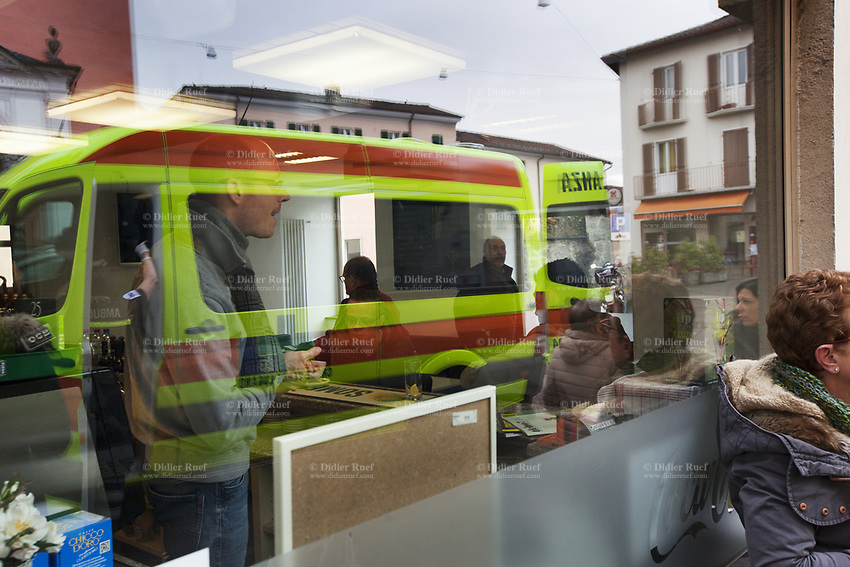 Switzerland. Canton Ticino. Stabio. Day scene for a medical emergency intervention. Ambulance's reflection in a cafe's window. Customers enjoy their morning coffee while others are outside smoking a cigarette. A senior man suffering from severe pains in the hip has to be brought to hospital by an ambulance from the Croce Verde Lugano. The Croce Verde Lugano is a private organization which ensure health safety by addressing different emergencies services and rescue services. 27.01.2018 © 2018 Didier Ruef
