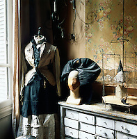 A tailor's dummy stands in the corner of a room dressed in old fashioned style clothing. The walls of the room have a neglected air with peeling wallpaper and plaster. A wire model with figurines and a model head stand on an old cabinet with many drawers.