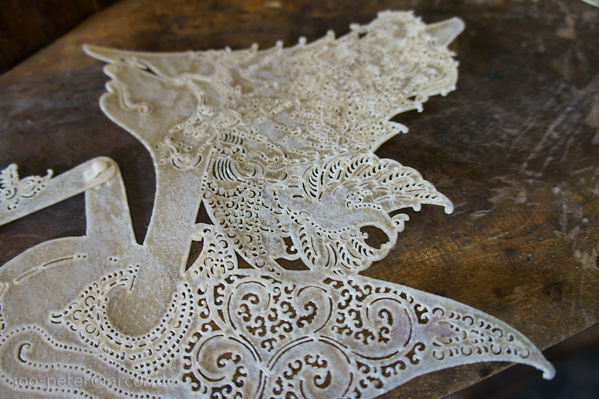 close-up of a wayang kulit leather puppet in the making - freshly cut, still without colours and painting - Yogyakarta, island Java, archipelago of Indonesia,  September 2011. Each ornament has a specific meaning (symbolizing for example water,fire, air or magic powers), this way traditional forms have to be followed precisely
