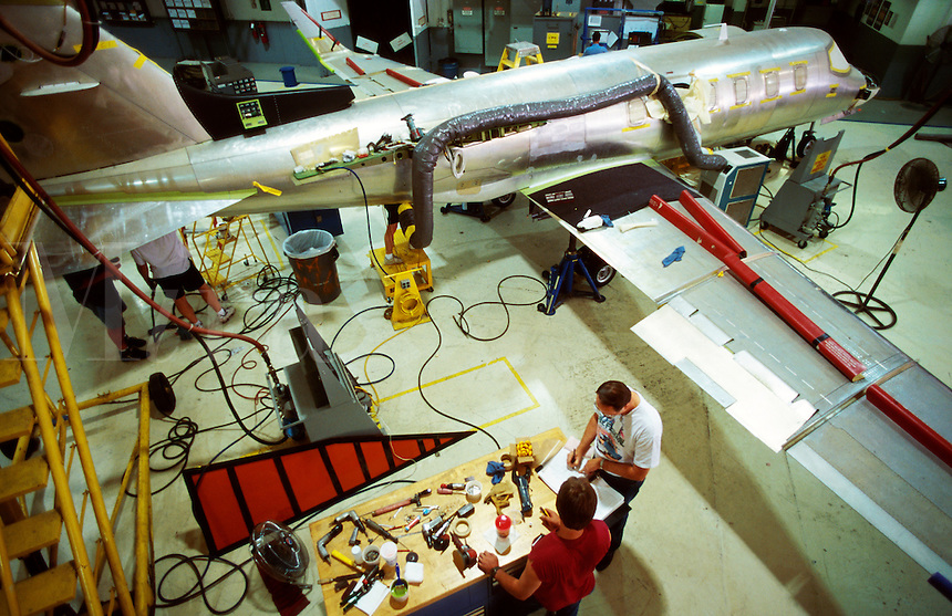 Overview of workers as they assemble components of a business jet on an assembly line.