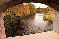 A bridge over the Manistique River with fall color along Ten Curves Road near Curtis Michigan.