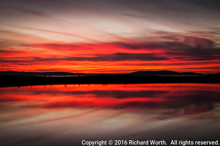 A small finger of land curves into San Francisco Bay, becoming the one-mile long par course for walkers and runners, and creating the small boat lagoon which, here, reflects the glowing fire of sunset.  San Leandro Marina Park.