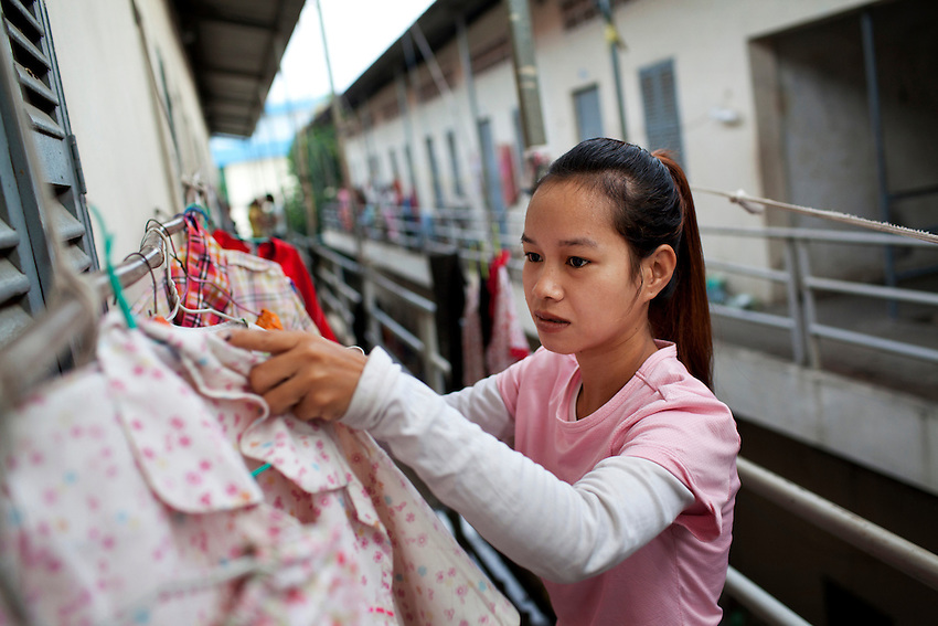 Keth Sreyroth, a 22-year-old worker at the Shen Zhou garment factory, hangs laundry outside the second storey room where she lives with 7 other factory workers, in a housing district near the Vattanac Industrial Park, in Phnom Penh, Cambodia, on September 15, 2011.