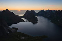 Setting sun over Bunesfjord and Kirkefjord from summit of Veinestind, Moskenesøy, Lofoten Islands, Norway
