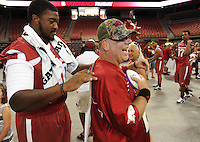 NWA Media/ANDY SHUPE - Richard Adcock of Little Rock, right, laughs as University of Arkansas junior tackle Grady Ollison of Malvern autographs an item for him during the annual  University of Arkansas Fan Day Sunday, Aug. 17, 2014, at Bud Walton Arena in Fayetteville. The day featured opportunities to have items autographed by members of the Razorbacks volleyball, soccer, football teams, mascots and the spirit squads. Visit photos.nwaonline.com to see more photos from the event.