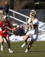 Boston College midfielder Cali Ceglarski (23) evades Boston University defender..Boston College (white) defeated Boston University (red), 12-9, on the Newton Campus Lacrosse Field at Boston College, on March 20, 2013.
