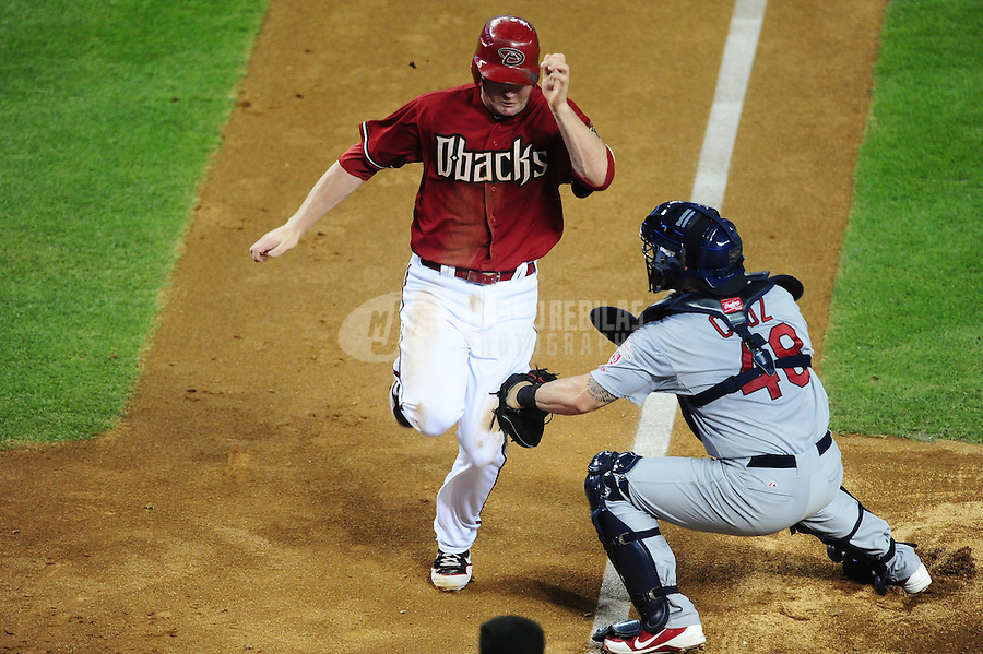 May 9, 2012; Phoenix, AZ, USA; St. Louis Cardinals catcher Tony Cruz (right) tags out Arizona Diamondbacks base runner Lyle Overbay in the fourth inning at Chase Field. Mandatory Credit: Mark J. Rebilas-