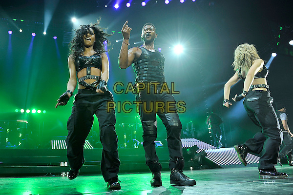 USHER (USHER RAYMOND).Performing live at the O2 Arena, London, England. .February 3rd, 2011.stage concert live gig performance music full length black leather singing backup dancers arm hand sleeveless vest jeans denim  .CAP/MAR.© Martin Harris/Capital Pictures.