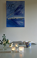 The contemporary dining table has a blue abstract picture hanging on the wall behind it