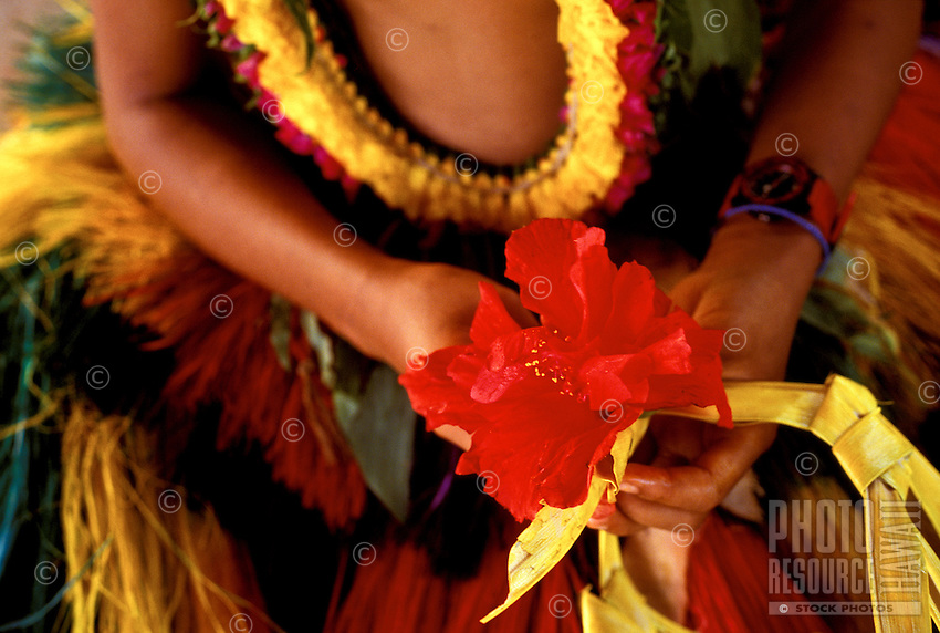Young native girl wearing traditional ceremonial costume and holding hibiscus flower prepares for a dance in Ma Village, Yap, Micronesia.