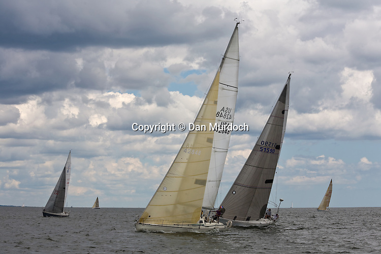 racing sailboats under a cloudy sky