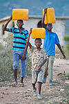 Boys carry water from a community water spigot provided by Servicio Social de las Iglesis Dominicanas in the Haitian community of Ganthier. SSID, a member of the ACT Alliance, has worked extensively in the community since it was devastated in 2016 by Hurricane Matthew.