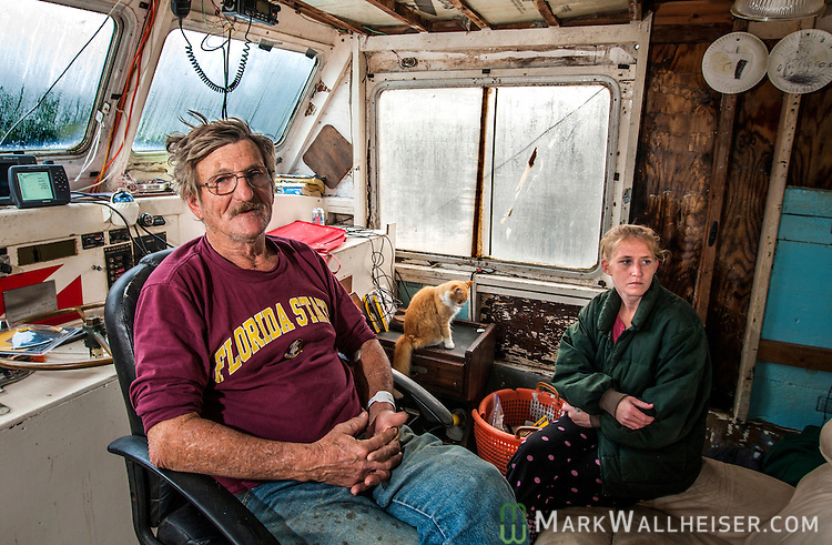 "Snow and sleet fall outside as 67 year-old Lawrence Snodgrass and his daughter-in-law Tiffany Johnson live on Snodgrass's 1967 boat ""Sprong"" where's he's lived for the past three years  in St Marks, FL .  Snodgrass fishes for grunts and sea bass to supplement his Vietnam veteran's benefit from the government.  Snodgrass just returned home after a couple of days in the hospital from a leg injury he received repairing his boat."
