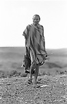 A Turkana man in the Suguta Valley, Northern Kenya.  In  his hands his spears and traditional pillow and foot stool.
