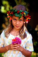 A young girl wearing a haku lei (flower headpiece) and a pretty dress holds a small bouquet of bougainvillea.
