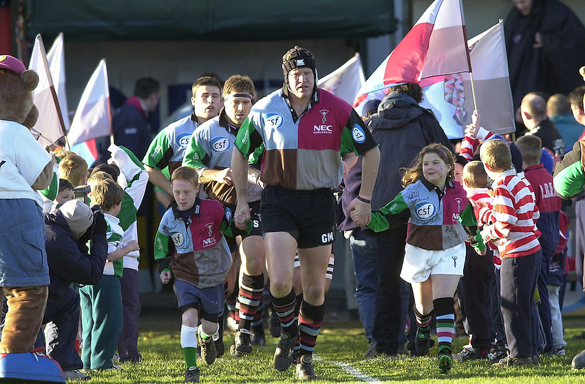 Photo Peter Spurrier.22/12/2001 Zurich Premiership.Harlequins v Leicester Tigers: The Stoop - Twickenham.Quins, Skipper Garrick Morgan runs out with the match's, junior mascots' for the day..............