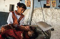 INDIA, Madhya Pradesh, children of organic cotton farmer at home, behind storage of harvested organic cotton / INDIEN, Kinder eines Biobaumwolle Farmers zu Hause, im Hintergrund geerntete Biobaumwolle