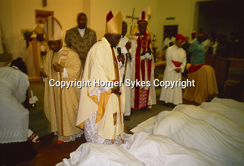 Black British Christian church London Uk Church of God of Prophecy, the enthronement of a new Bishop. Members of the congregations prostrate themselves before him.