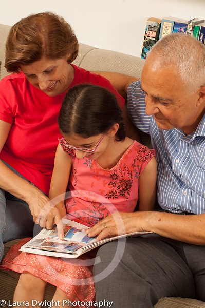 8 year old girl at home with grandparents showing them photo album