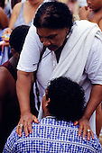 Salvador, Bahia State, Brazil; Laying on of hands in a spiritualist healing ceremony.