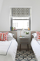The subtle introduction of colour has been created in this bedroom through red piping on the upholstered headboards, cushions and the patterend carpet