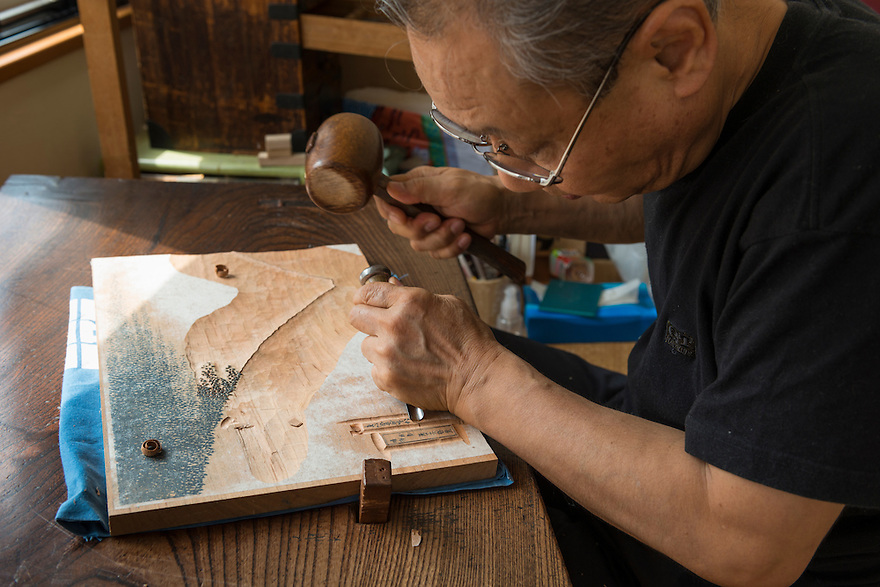 Woodblock carver Moichika Niinomi works on a reproduction of Katsushika Hokusai's Fine Wind, Clear Morning. Adachi Foundation for the Preservation of Woodcut Printing, Tokyo, Japan, July 15, 2014. The Foundation works to preserve the original techniques of Japanese woodblock printing. As well as recreating classic ukiyo-e from the Edo period, they train and employ young artisans, and also educate about the art form.