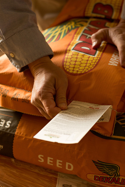 April 20, 2016. Rowland, North Carolina. <br />  Bo Stone looks over the label of one the types of GM corn seed that he grows. <br />  Bo Stone, age 44, runs a 2300 acre farm near the South Carolina border. After 5 generations of tobacco farming, Stone helped to move his family farm over to corn, wheat, soybeans, and strawberries 7 years ago. <br />  While his corn crop is entirely made up of stacked genetically modified strains of corn, Stone says he chose the varieties primarily for their yield characteristics, but having the ability to utilize their herbicide tolerant traits if a weed gets out of control is &quot;another tool in my toolbox&quot;.