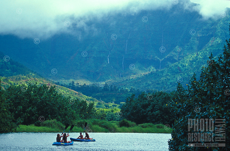 Girls paddling kayaks on the Hanalei River with ran shrouded Mount Waialeale and waterfalls in background, Kauai, Hawaii