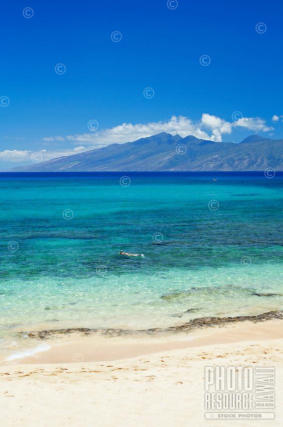 A snorkeler enjoying a beautiful day at Kapalua, Maui, with Moloka'i in the distance.