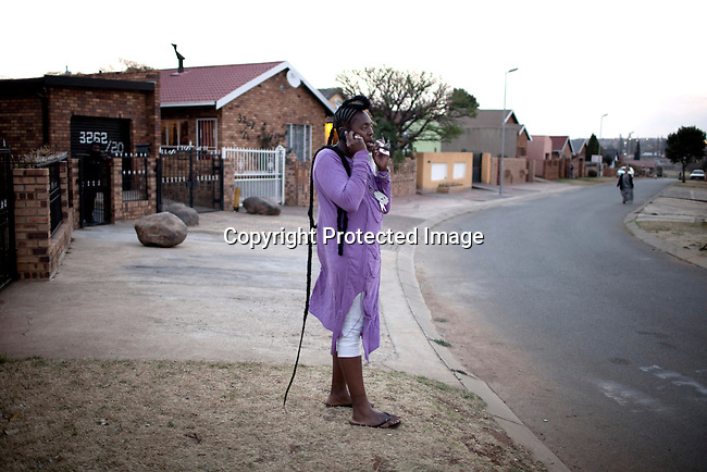 SOWETO, SOUTH AFRICA AUGUST 25: Sibu FDB, a young designer part of the collective group Smarteez chats on the phone with a client outside his family house on August 25, 2012 in the Rockville section of Soweto, South Africa. Known for their street style fashion they had a great opportunity recently to show their township inspired designs at South African fashion week. Soweto today is a mix of old housing and newly constructed townhouses. A new hungry black middle-class is growing steadily. Many residents work in Johannesburg but the last years many shopping malls have been built, and people are starting to spend their money in Soweto. (Photo by: Per-Anders Pettersson)