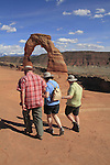 Older hikers at Delicate Arch in Arches National Park, Moab, Utah, USA. .  John offers private photo tours in Arches National Park and throughout Utah and Colorado. Year-round.