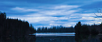 """""""WOAHINK WONDER""""<br /> <br /> Beautiful moody blue winter skies and dark forests accentuate this alluring landscape which is a refection upon the waters of Woahink Lake in Oregon."""