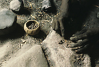 The pellets are crushed, to eliminate as much slag as possible, and are placed in a crucible made of clay taken from an inhabited termite-ant mound which contains high levels of quartz, similar to the one used for the wind-tube