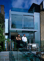 Home owners Bernard and Emma Shapero standing on the terrace outside the modern glass extension to their London home