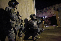 soldiers of C Company, 1st battalion, 506th, 101st airborne division move to their target providing security towards eachother  while conducting a night raid with the purpose of arresting two suspected major figures of the Sunni insurgency in their sector in Eastern Ramadi, Al Anbar province, Iraq on WED Jan 11 2006. the mission was divided into two sections. SECTION ONE  with the prurpose of blocking the suspected insurgents from escaping and providing sniper fire for the area and SECTION 2 raiding the house were the two were suppose to be hiding. the two suspected insurgents were nt to9o be found.