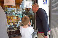 Father and son shopping for pastries in bakery window. Tomaszow Mazowiecki Central Poland
