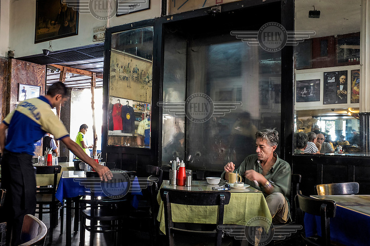 A tourist drinks tea in Cafe Leopold in Colaba. The iconic landmark was one of the targets during the 2008 Mumbai terror attacks. Ten people were killed when terrorists sprayed the cafe with bullets for around 90 seconds. Scars from the assault remain, leaving the interior marked with bullet holes.